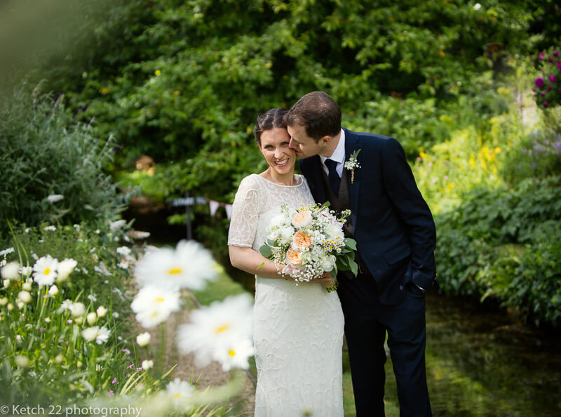 Groom kissing bride in beautiful Cotswold garden at Wedding at The Swan Bibury