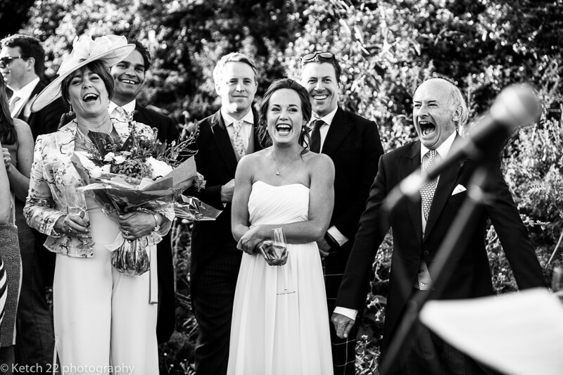 Mum and Dad laughing during speeches at Dorset summer wedding