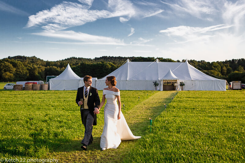 Bride and groom in front of Marquee at Dorset summer wedding
