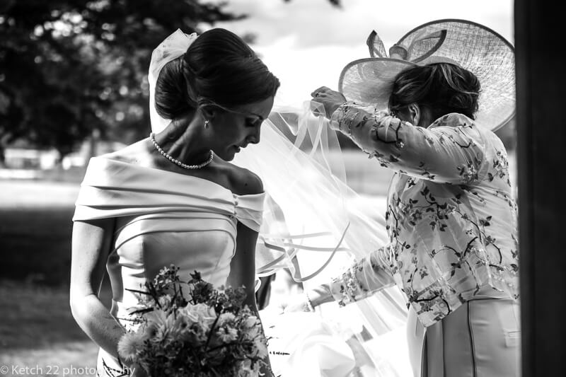 Black and white photo of Mum getting bride ready before wedding ceremony in Dorset