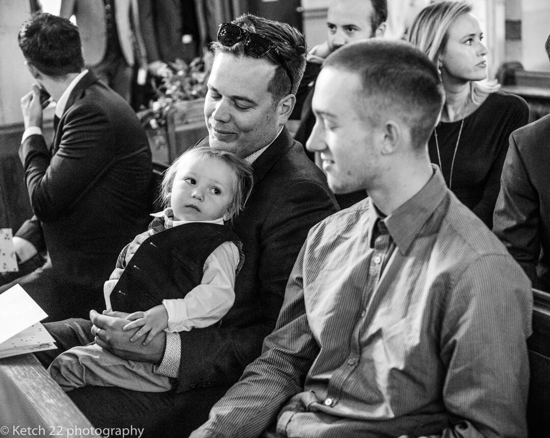 Cute small boy looking at his family just before wedding ceremony