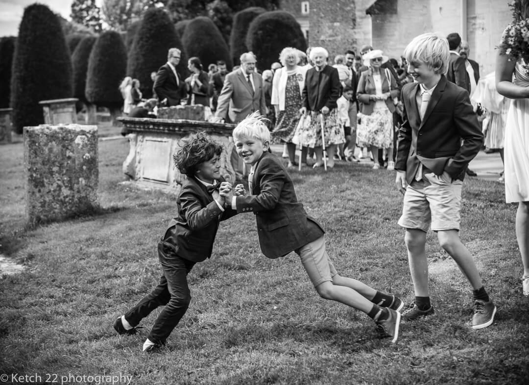 Kids playing in church grounds at Gloucestershire wedding