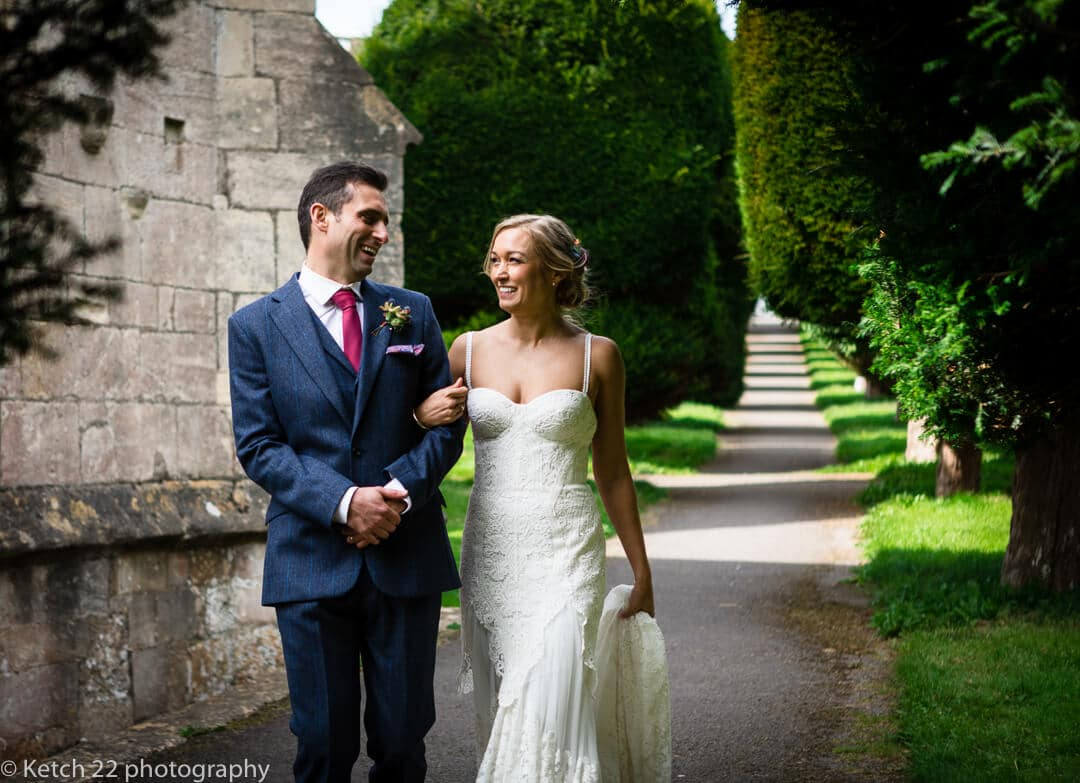 Natural, relaxed portrait of bride and groom outside Painswick church