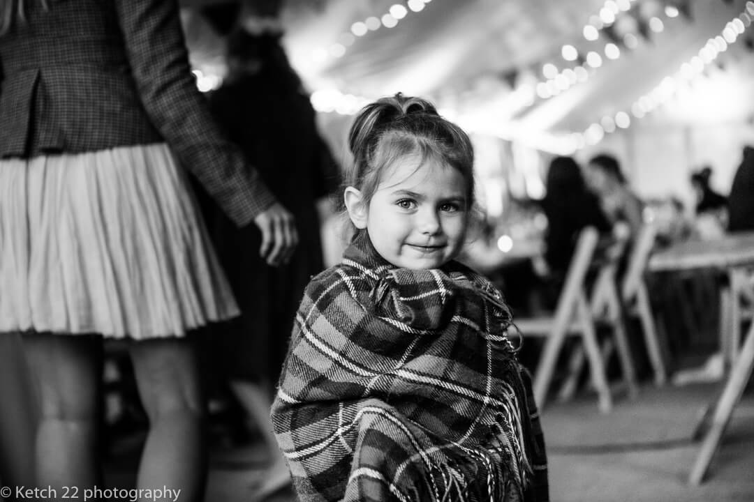 Cute little girl wrapped in blanket at summer wedding