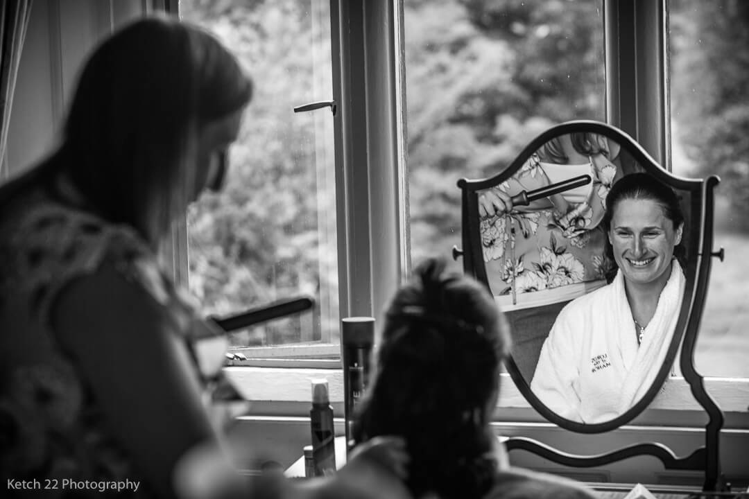 Bride looking in mirror at wedding preparations