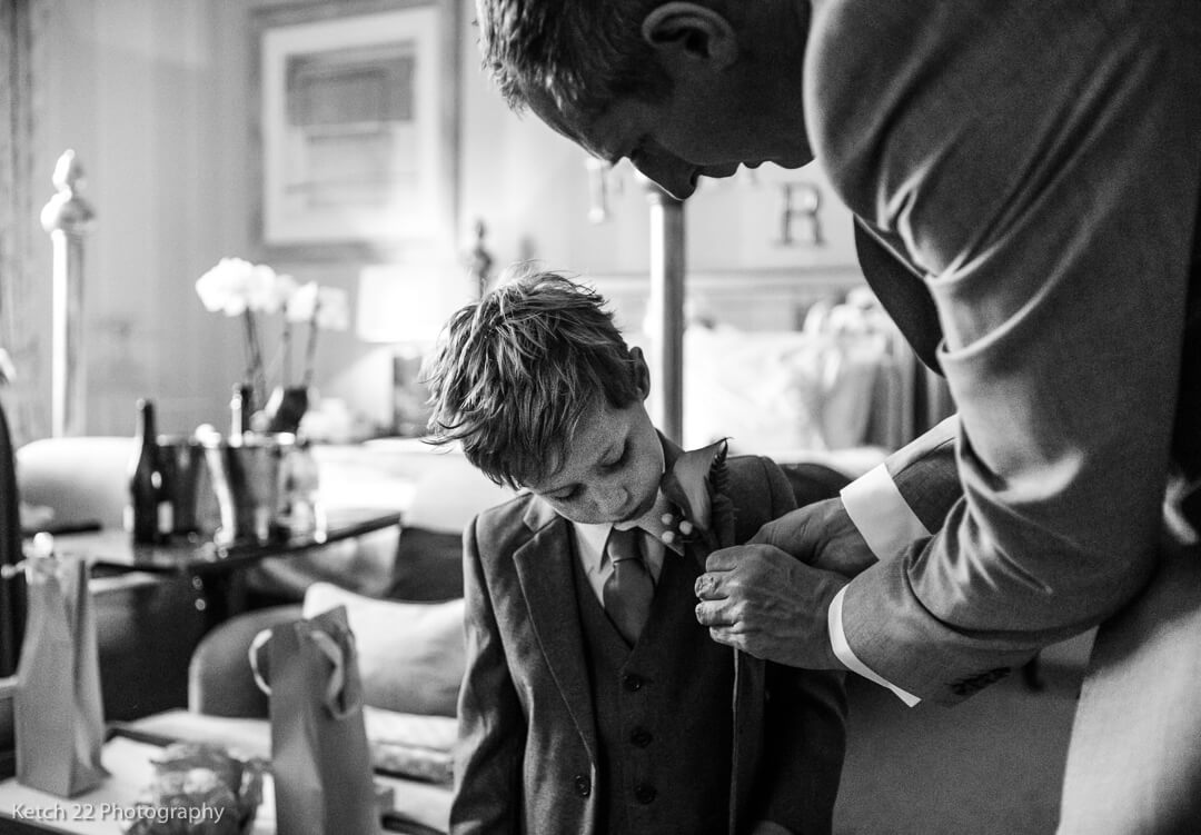 Page boy having flower attached to jacket at wedding