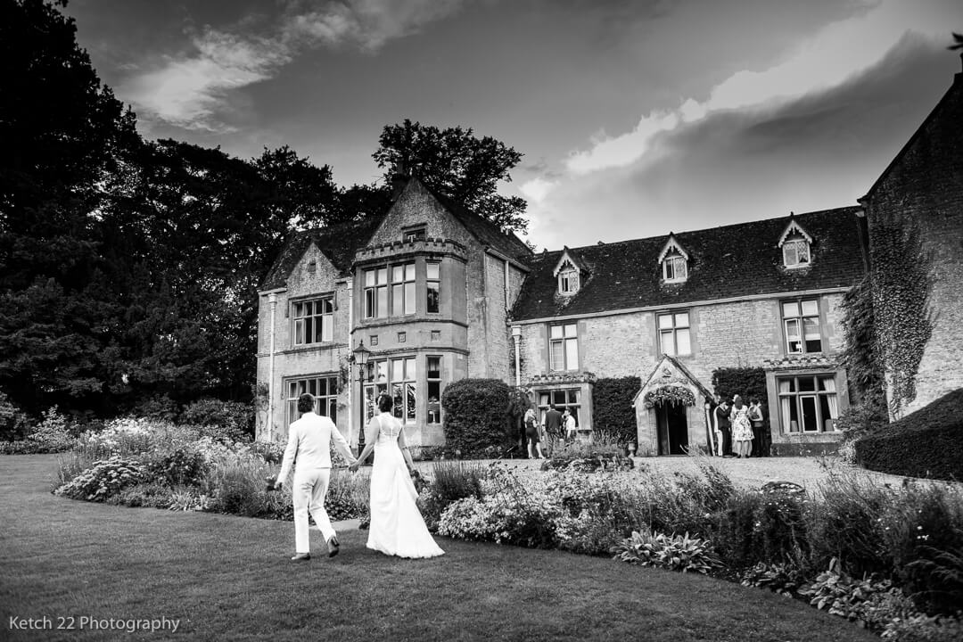 Newly weds walking in front of The Lords of the Manor wedding venue
