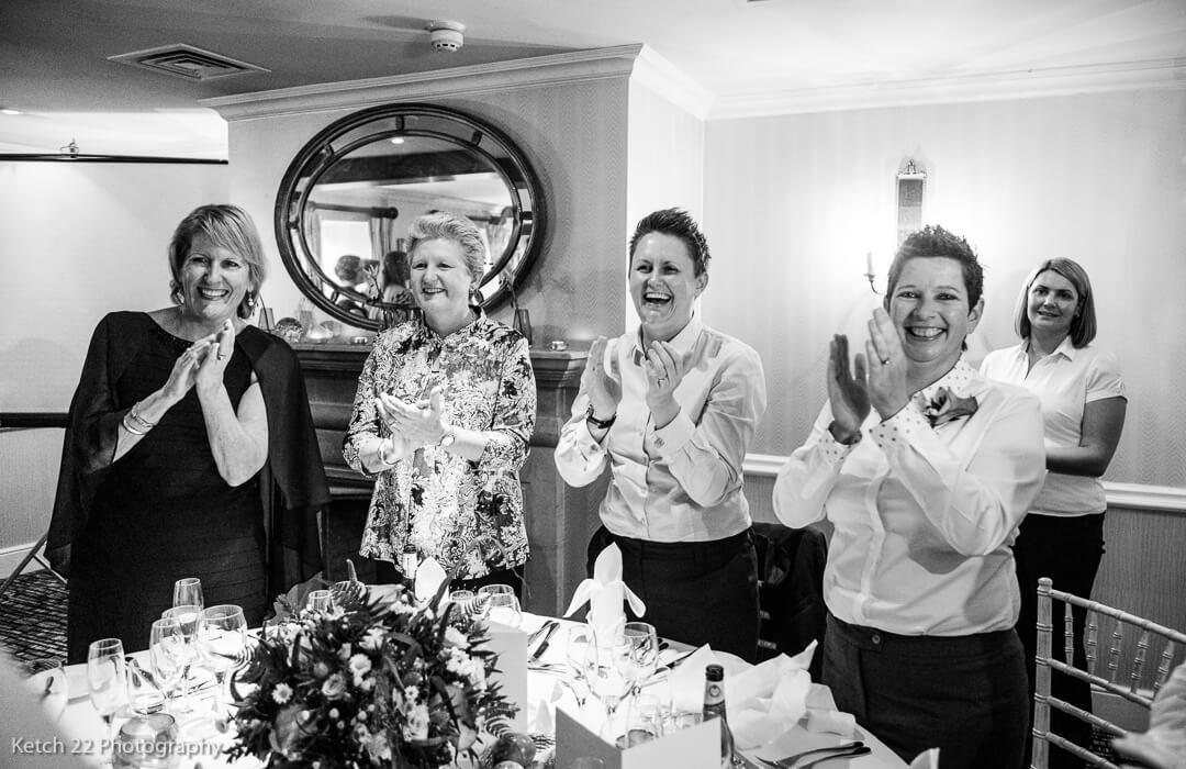 Wedding guests cheering as bride enters dining room