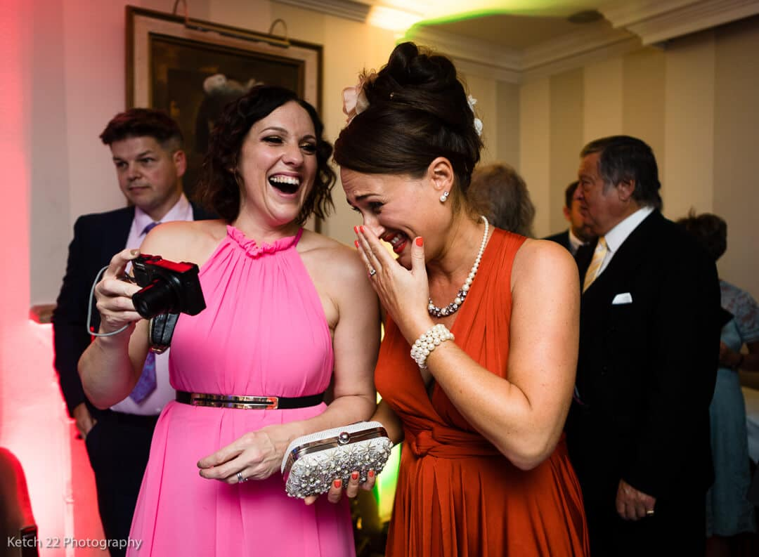 Wedding guests with pink and red dresses laughing at reception