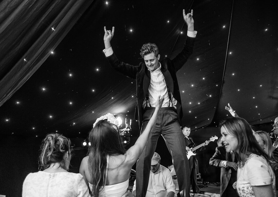 Groom standing on table dancing at wedding reception