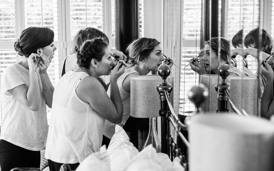Bridesmaids putting make up on in mirror at Hilles House Wedding