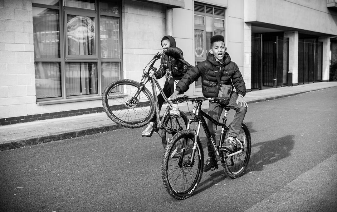 Kids doing wheelys on bicycles at Gloucester docks