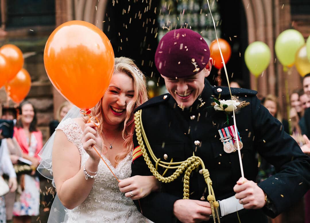 Bride with orange balloon and groom with purple army beret get showered with confetti