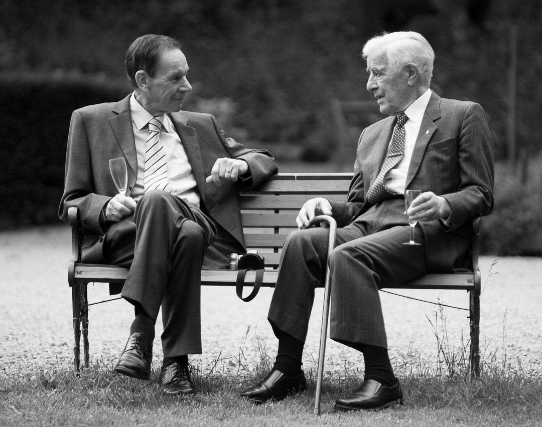 An example of a documentary weddings photograph of two Grandad's chatting on a bench