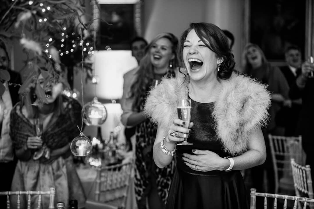 Natural documentary weddings photo of Bridesmaid laughing at speeches