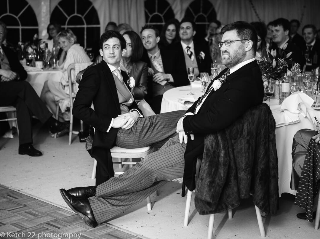 Groom and best man listening to wedding speeches