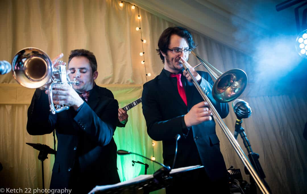 Saxophone and trumpet players in wedding band performing