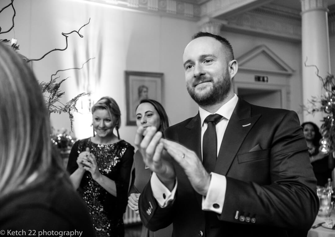 Wedding guests cheering as bride and groom enter dinning room