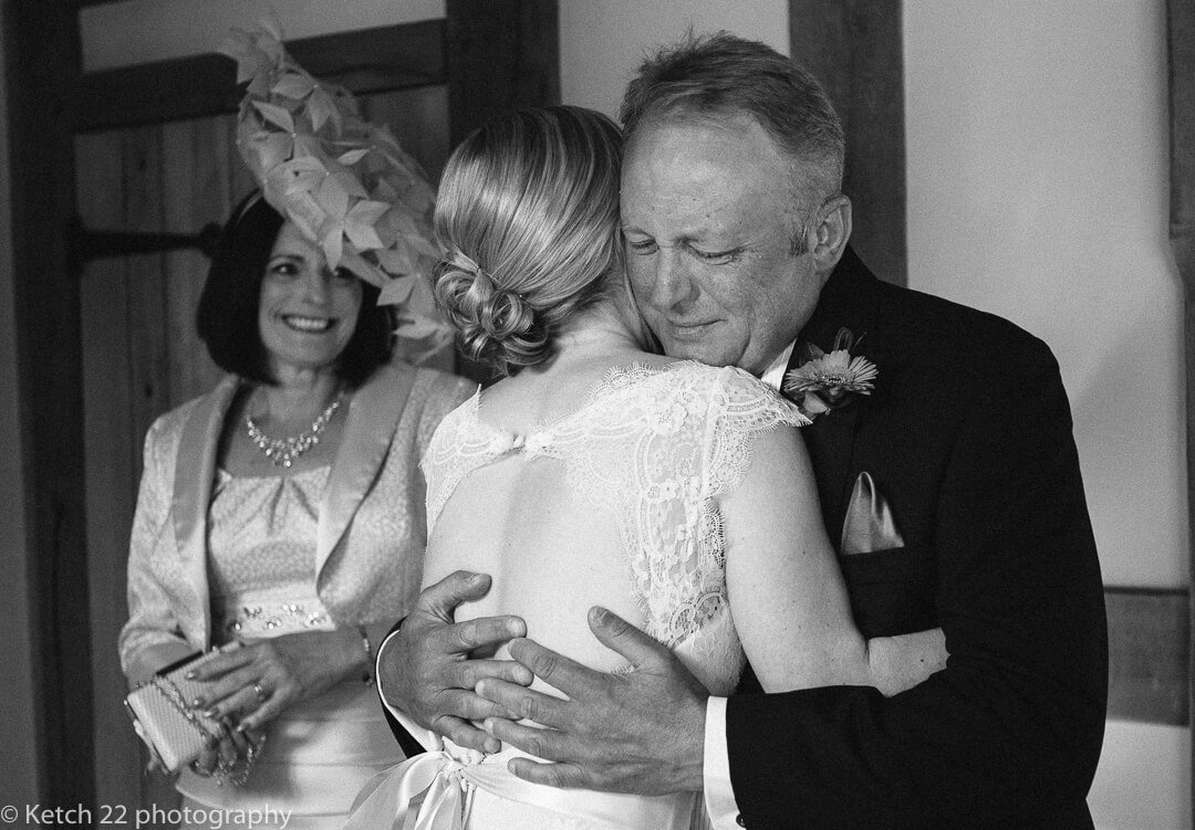 Storytelling wedding photography of bride giving her father an emotional hug