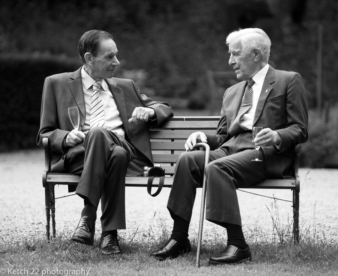 Two old men chatting at wedding