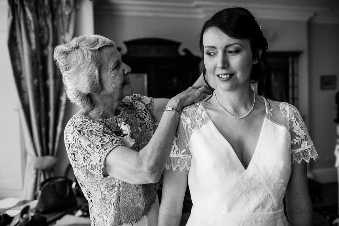 Mother of bride helping her daughter get ready at Country House wedding