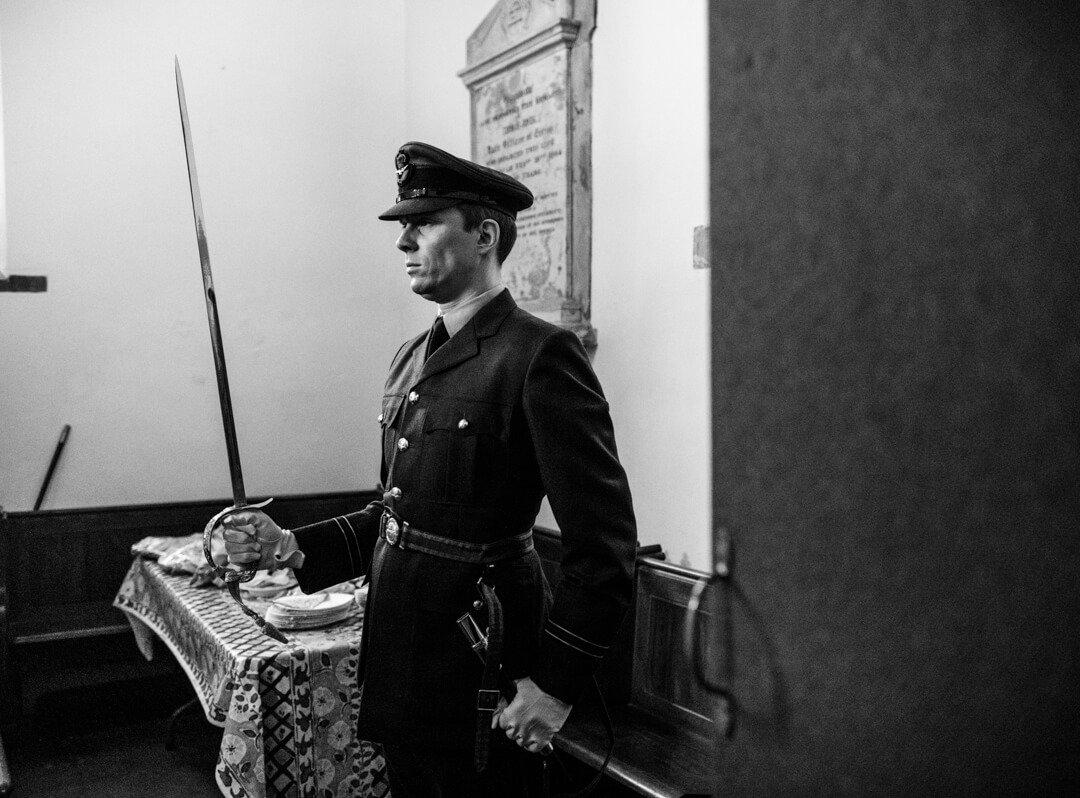 Groomsmen in RAF uniform standing guard with sword at wedding