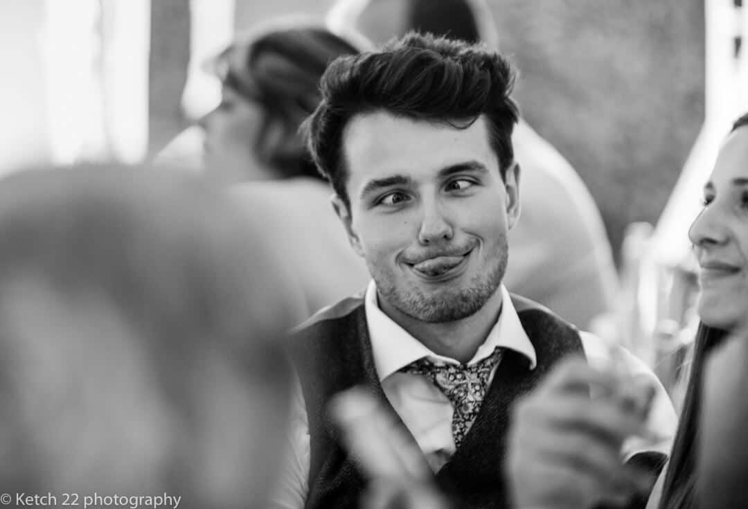 Groomsmen sticking his tongue out and crossing his eyes