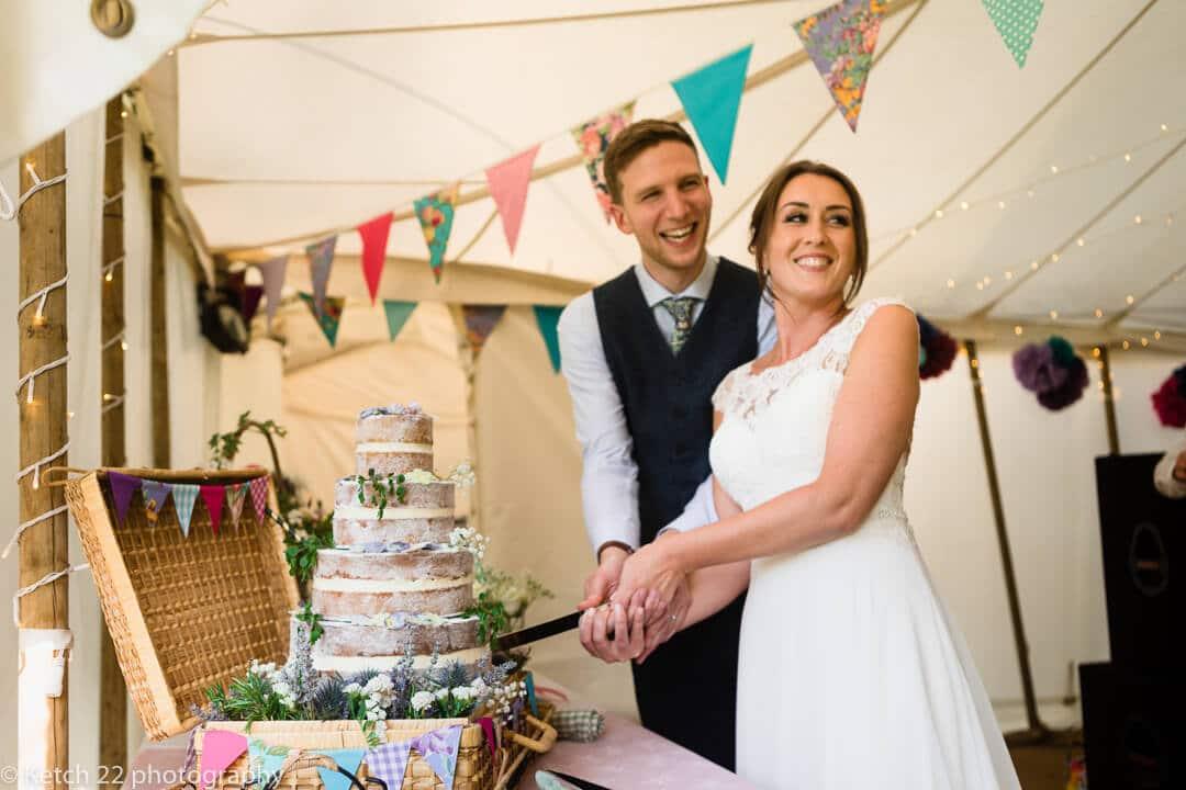 Bride and groom cutting vintage wedding cake