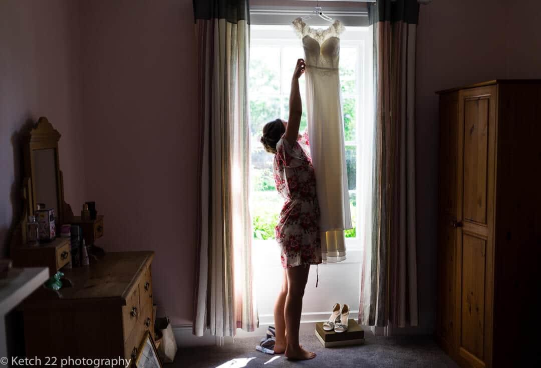 Bride hanging up her wedding dress