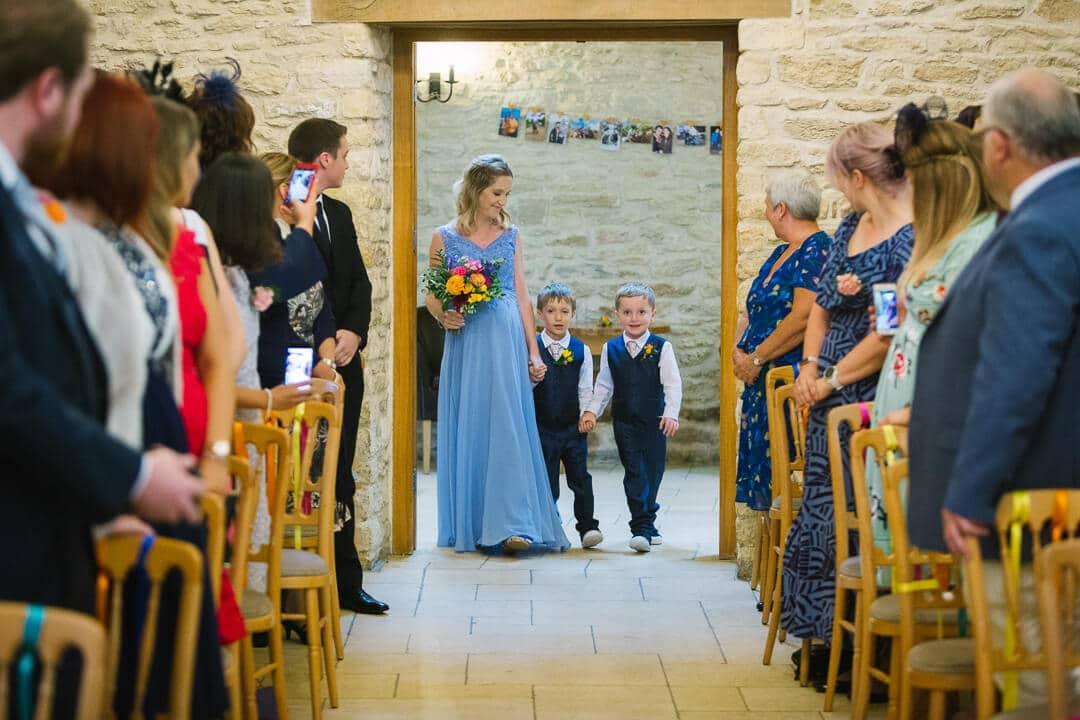 Bridesmaid and page boys enter wedding ceremony