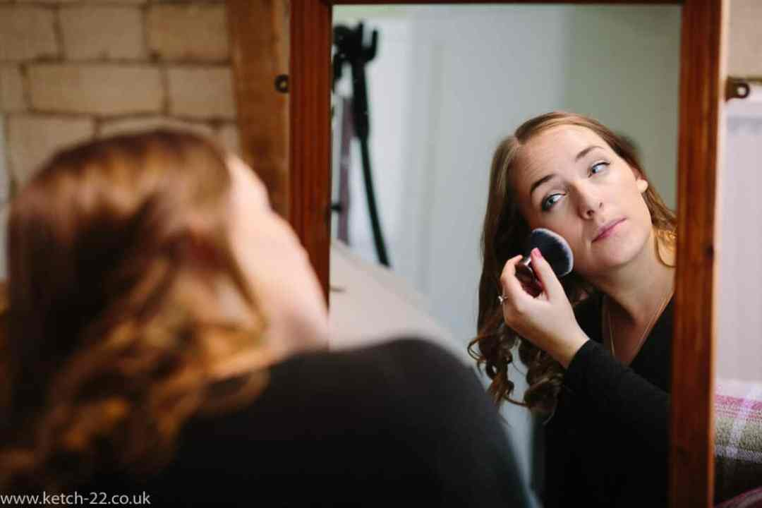 Bridesmaid powdering her face at wedding preparations