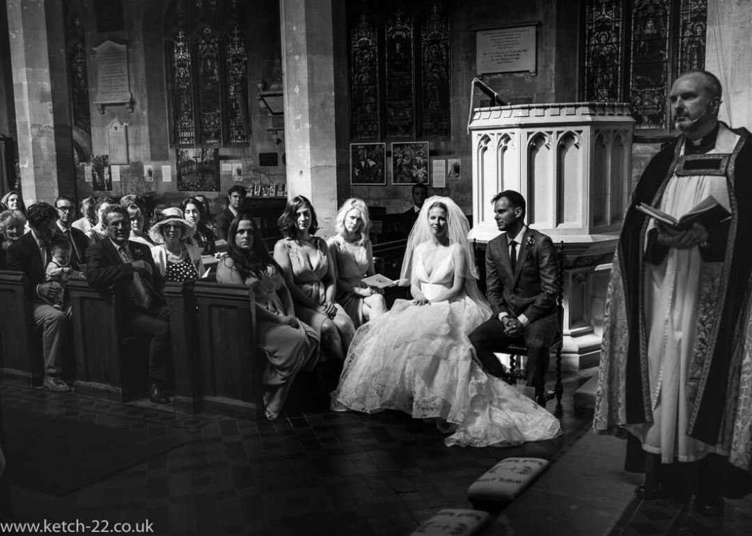 Bride and groom listening to vicar talk at Church wedding