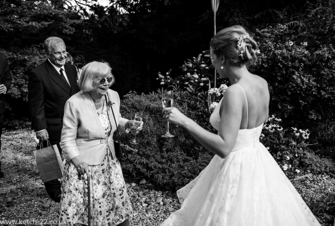 wedding documentary photo of grand ma greeting bride