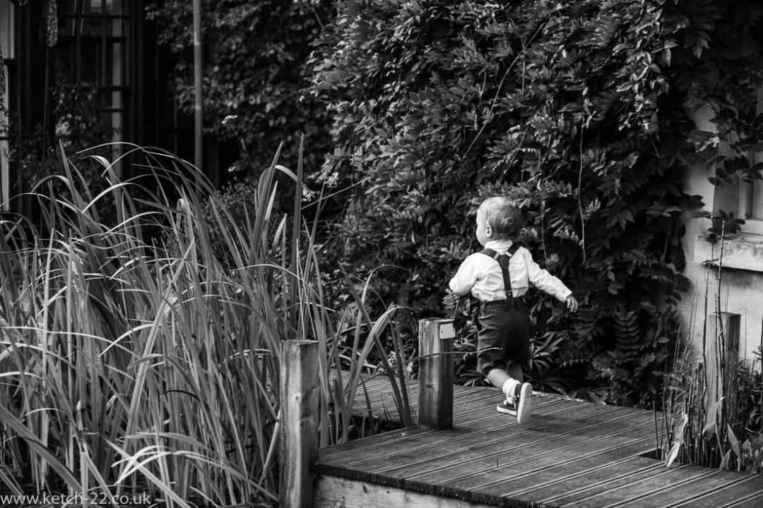 Page boy running in garden at Gloucestershire wedding