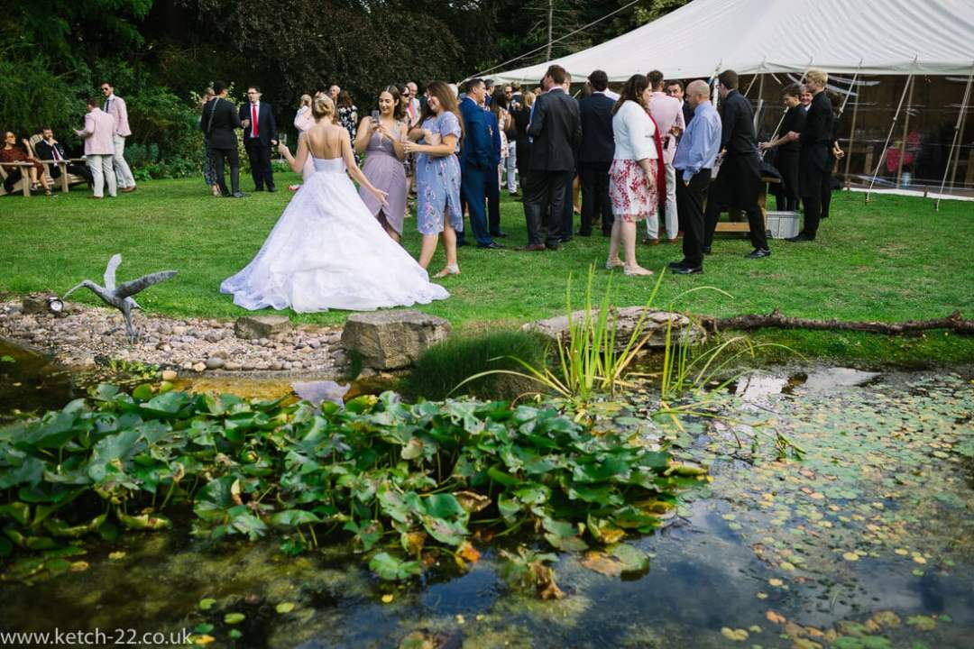 View of lilly pond and wedding guests in garden