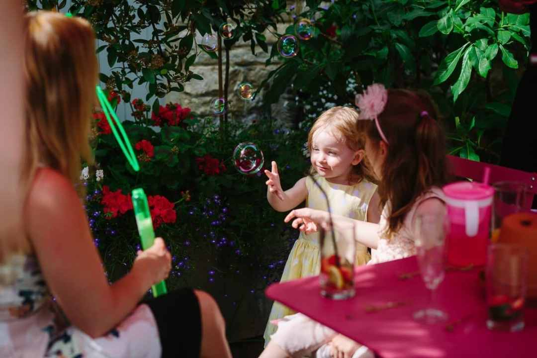 Kids play with bubbles at wedding