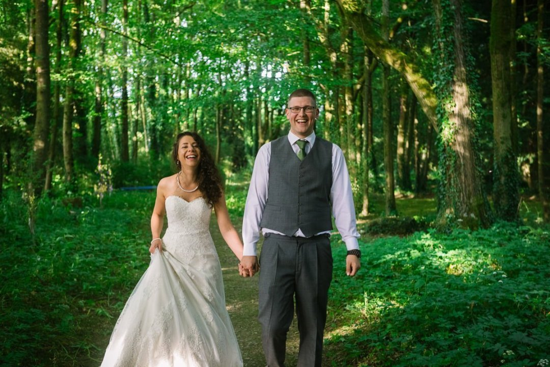Bride and groom walking in green woods
