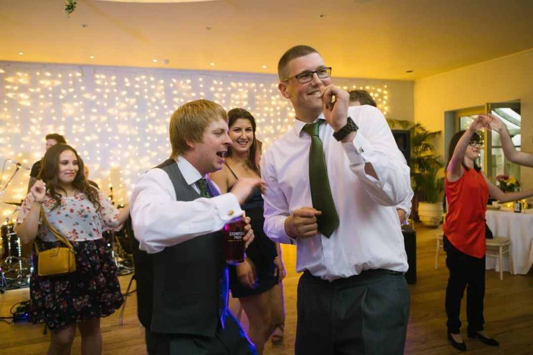 Groom and best man dancing at wedding reception
