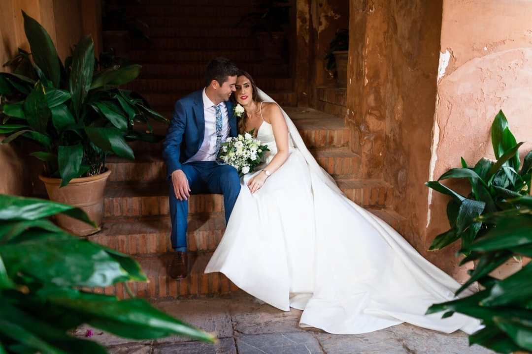 Portrai of bride and groom sitting on steps at Spanish wedding
