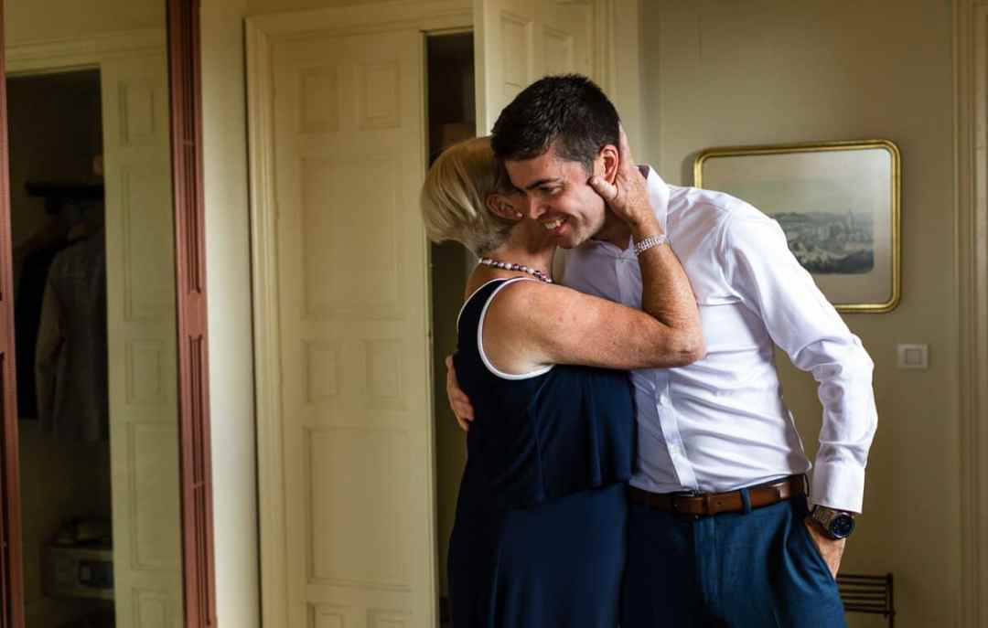 Mother of groom hugging her son during wedding preparations