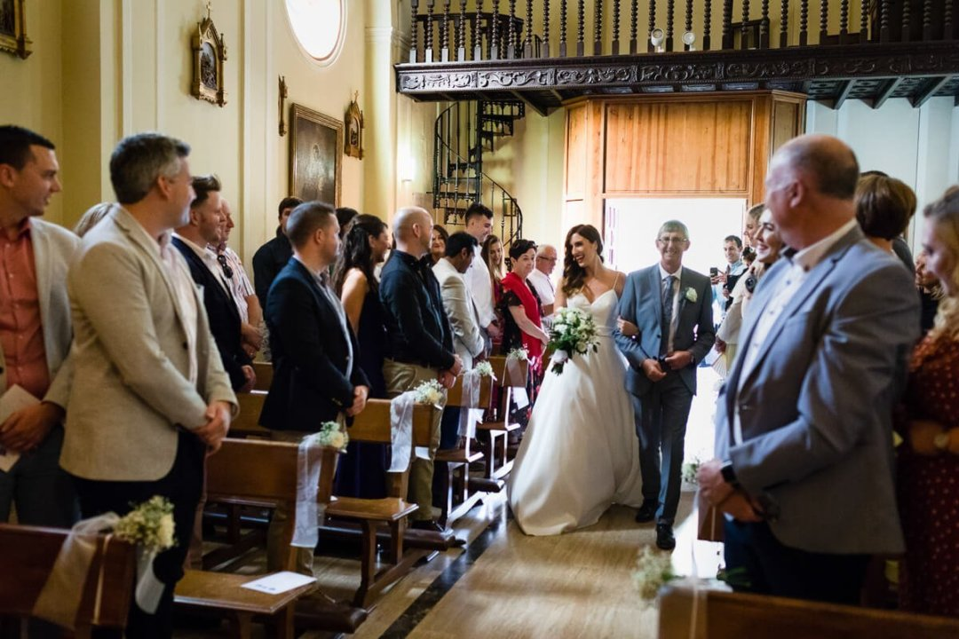 Father of bride walking down church aisle with daughter at Wedding in Malaga Spain