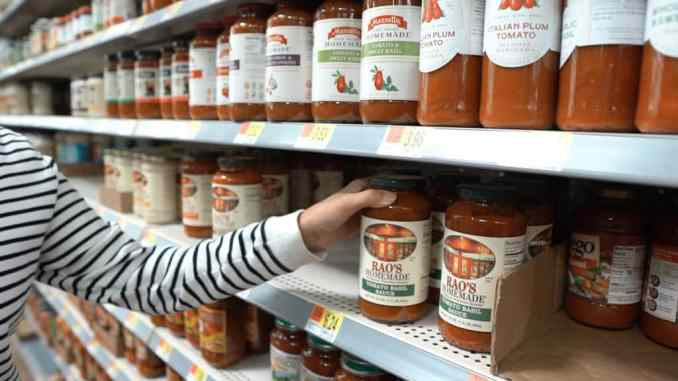 hand reaching for marinara on a shelf next to other sauces