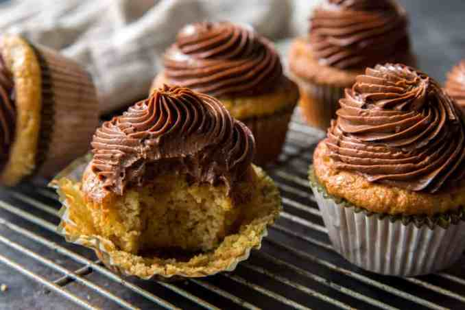 chocolate frosted keto cupcakes in paper muffin liners on a cooling rack
