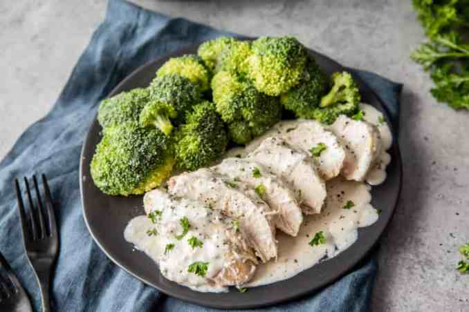 instant pot creamy chicken sliced and served on a black plate with broccoli