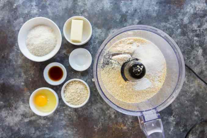 Food processor next to the ingredients to make oatmeal cookies