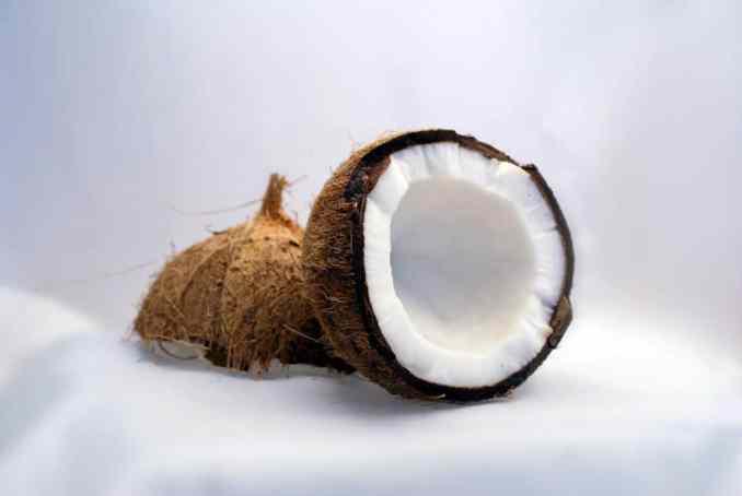a coconut broken in half on top of sand