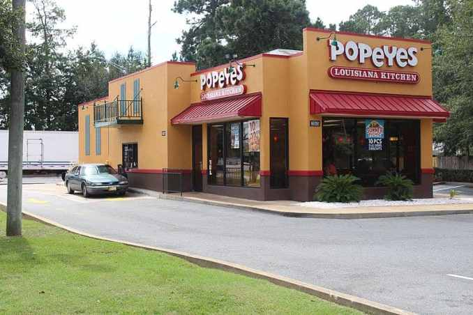 yellow popeyes building with red awnings