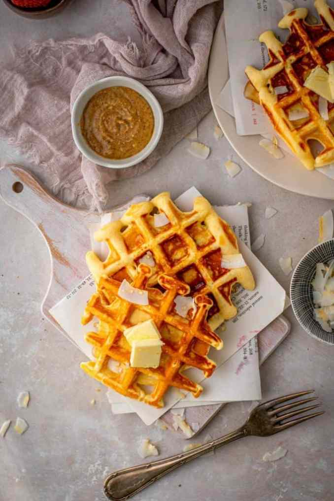 Buttered protein waffles next to coconut flakes, almond butter, and a silver fork.