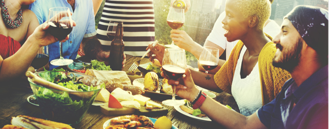 A group of people sharing a dinner and a glass of wine