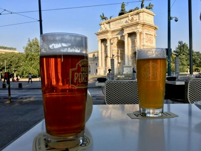 An aperitivo featuring two glasses of Poretti beer, with Milan's landmark the Arco della Pace in the background. ©KettiWilhelm2017